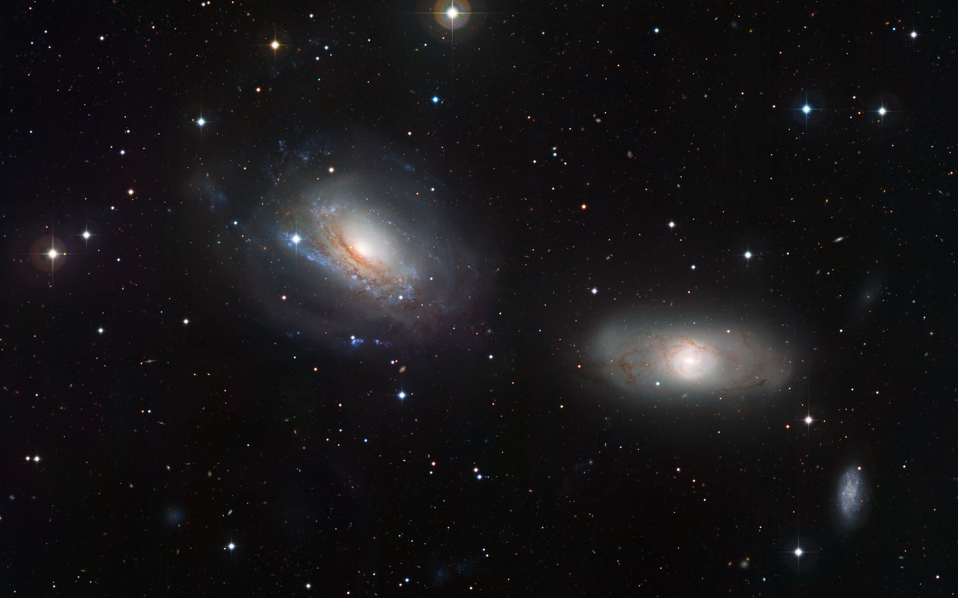 This image from the Wide Field Imager on the MPG/ESO 2.2-metre telescope at the La Silla Observatory in Chile captures the pair of galaxies NGC 3169 (left) and NGC 3166 (right). These adjacent galaxies display some curious features, demonstrating that each member of the duo is close enough to feel the distorting gravitational influence of the other. The gravitational tug of war has warped the spiral shape of one galaxy, NGC 3169, and fragmented the dust lanes in its companion NGC 3166. At the bottom-right of the pair, a third galaxy is portrayed, NGC 3165.